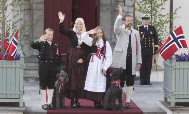 SKAUGUM: Kronprinsfamilien hilser barnetoget på Skaugum 17. mai. Fra v. prins Sverre Magnus (med hunden Muffins Kråkebolle), kronprinsesse Mette-Marit, prinsesse Ingrid Alexandra (med hunden Milly Kakao) og kronprins Haakon. Foto: Terje Pedersen / NTB scanpix