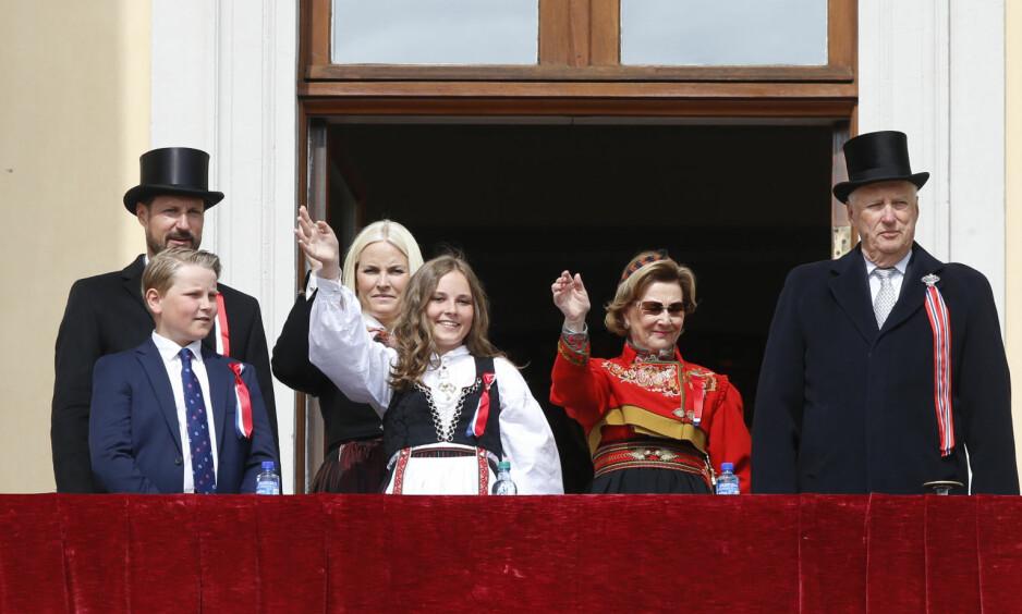 BRYTER ETIKETTE: Dronning Sonja, Mette-Marit og Ingrid Alexandra bryter bunadsetikette mens de vinker til barnetoget fra slottsbalkongen. Foto: NTB Scanpix