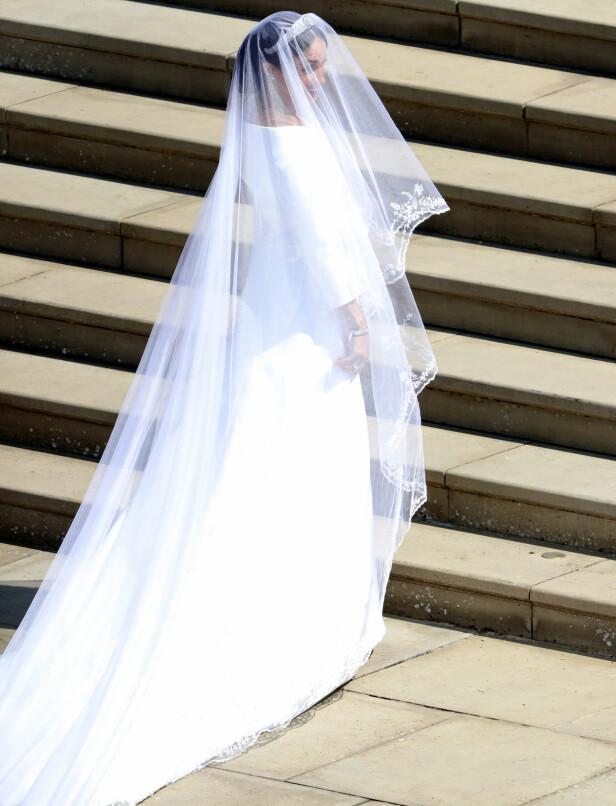 HER ER BRUDEN. Meghan Markle på vei inn til vielsen i sin kjole fra det franske motehuset Givenchy - men designet av britiske Clare Waight Keller. Foto: NTB scanpix