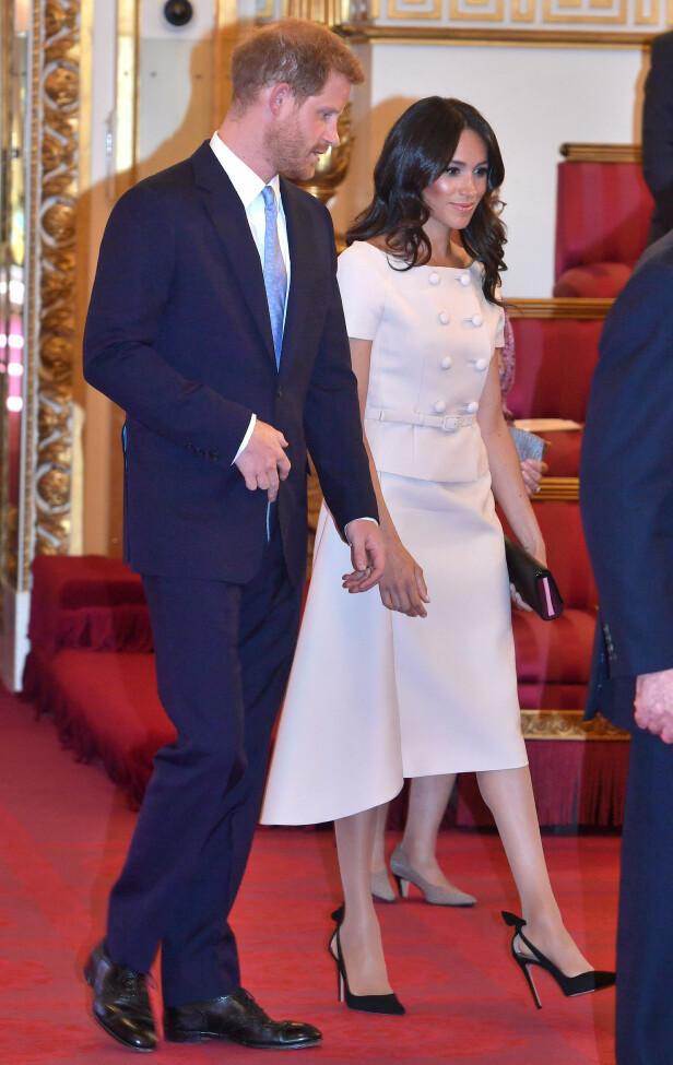 STRÅLTE: Hertuginne Meghan ankom sammen med prins Harry og dronning Elizabeth i en blekrosa kjole fra motehuset Prada. Legg merke til at skoene igjen ser litt romslige ut. Foto: NTB Scanpix