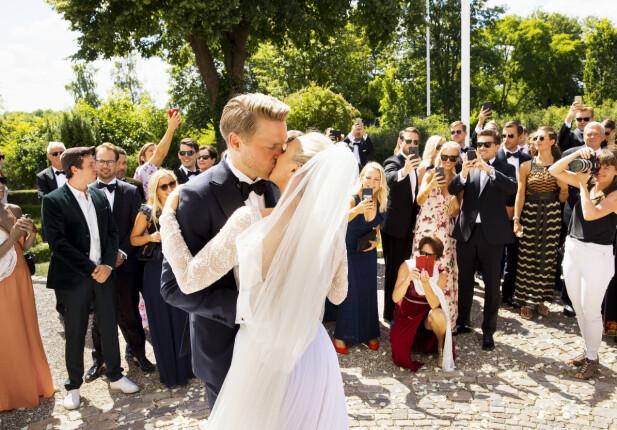 <strong>KYSS:</strong> Det ble aldri nok kyssing. Så snart brudeparet ankom slottsplassen krevde gjestene et nytt. Foto: Espen Solli / Se og Hør