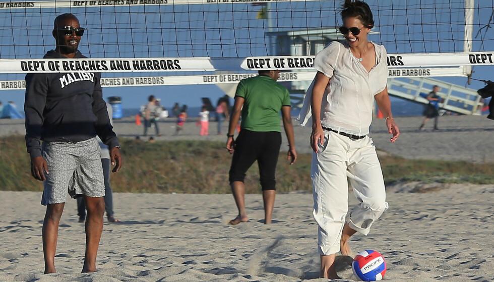 GOD STEMNING: Latteren satt løst da paret var på stranda i Mailbu. De tok seg både tid til kosing med hverandre, og volleyball. Foto: NTB Scanpix