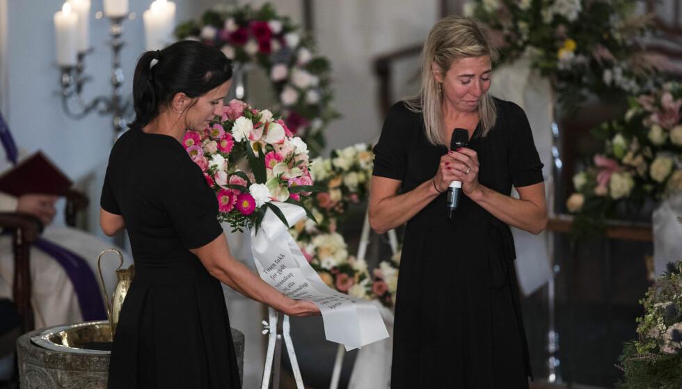 <strong>FARVEL:</strong> Marit Bjørgen og Kristin Størmer Steira leser fra blomsterkransene under begravelsen til Skofterud fra Eidsberg kirke torsdag. Foto: Trond Reidar Teigen / NTB scanpix