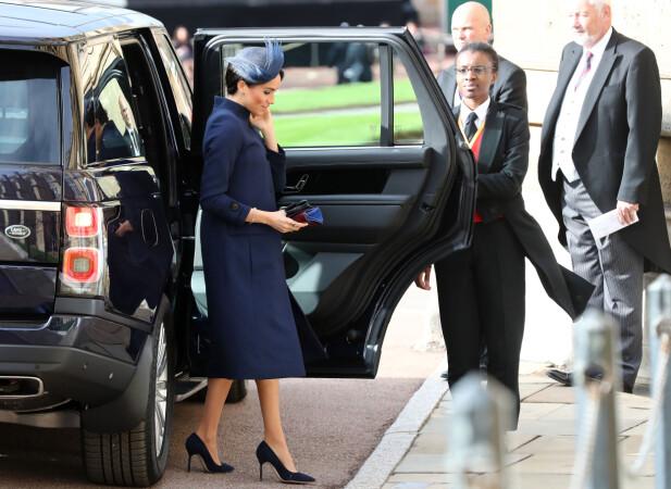 DEKKET TIL MAGEN: På vei inn til vielsen til prinsesse Eugenie og Jack Brooksbank fredag, var hertuginne Meghan iført en løstsittende kåpe. Foto: NTB scanpix