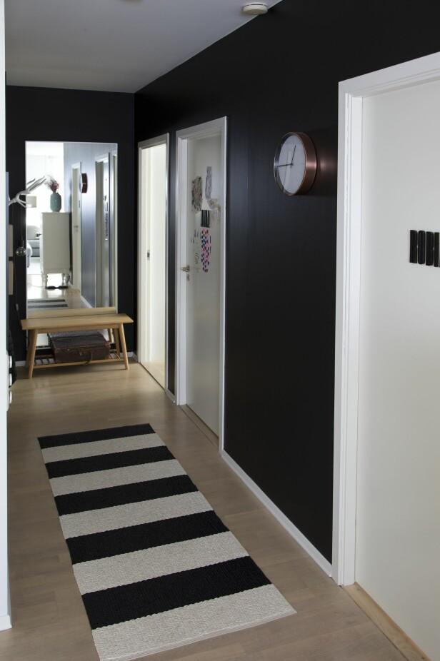 KONTRAST: Mens stue og kjøkkenet er malt i lyse farger, har paret valgt å ha gangen mørk. Foto: Tor Kvello/ Se og Hør
