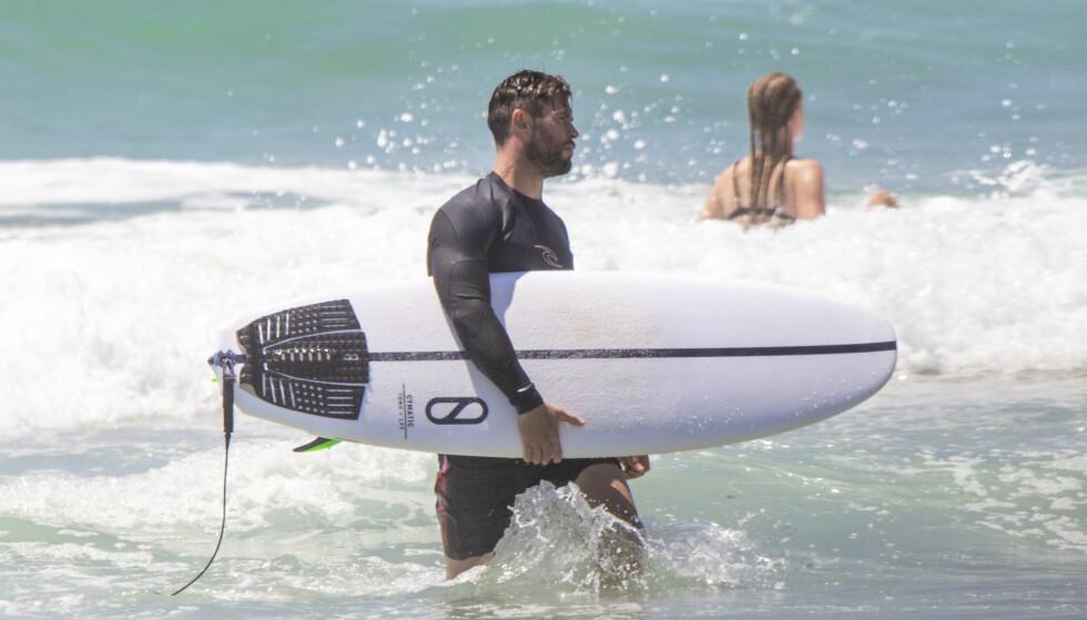<strong>SPORTY:</strong> Chris Hemsworth er glad i å bevege seg, og når han ser en mulighet til å surfe tar han den på strak arm. Foto: NTB Scanpix