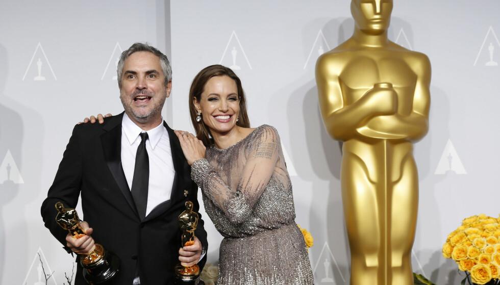 NÆRKONTAKT: Angelina poserte tett på Alfonso i presserommet på Oscar-utdelingen i 2014, etter at hun hadde gitt ham én av kveldens to Oscar-statuetter. Foto: Reuters/ NTB scanpix