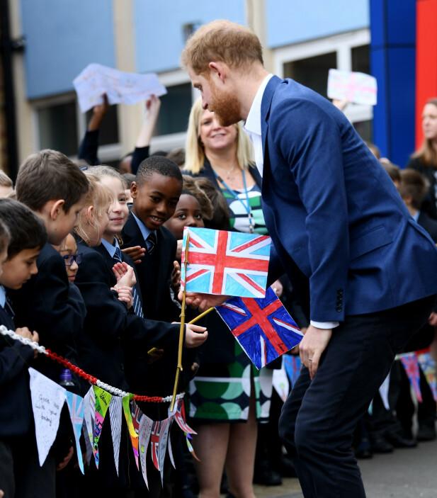 VARM VELKOMST: Flere av elevene fra skolen sto klare til å ta imot prins Harry med hjemmelagde flagg. Foto: NTB scanpix