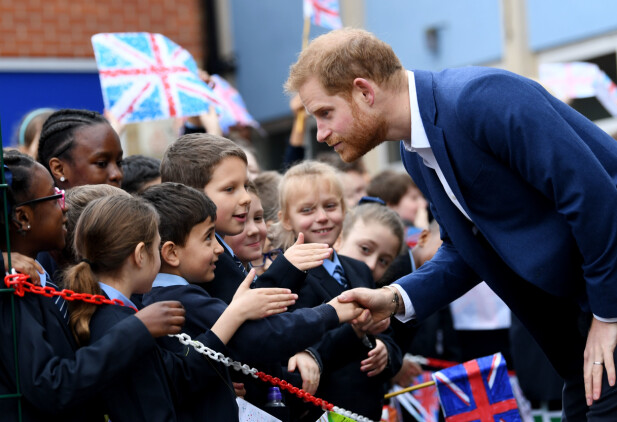 TOK SEG GOD TID: Den britiske prinsen tok seg god tid til å hilse på alle elevene som sto utenfor med flagg og velkomstskilt. Foto: NTB scanpix