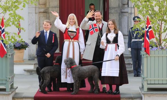 BUNAD: Kronprins Haakon, kronprinsesse Mette-Marit og prinsesse Ingrid Alexandra har alle på seg bunad. Prins Sverre Magnus har for anledningen på seg dress, og også familiens hunder er pyntet til 17. mai med sløyfer rundt halsen. Foto: Andreas Fadum