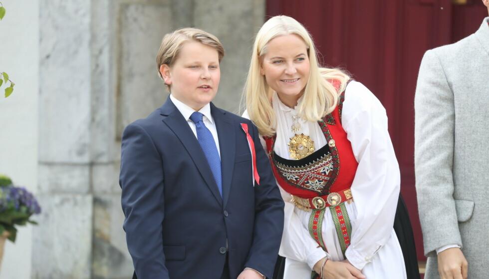 MOR OG SØNN: Kronprinsesse Mette-Marit og prins Sverre Magnus. Sistnevnte har de siste årene hatt på seg bunad, men gikk i år for en mørkeblå dress. Foto: Andreas Fadum