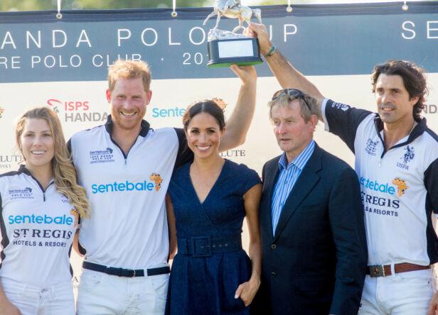 I FJOR: Her holder prinsen og Figueras en pokal høyt i været etter en seier i fjor sommer. Hertuginne Meghan er også med. Foto: NTB Scanpix