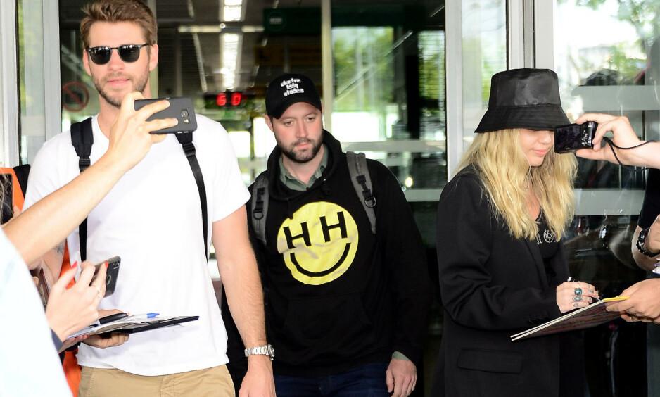 <strong>SVARER:</strong> Den amerikanske sangeren Miley Cyrus er blant de mest populære artistene i verden. Nylig ble hun antastet av en fan i Barcelona, noe hun ikke finner seg i. Her er hun og ektemannen Liam Hemsworth (t.v.) utenfor flyplassen i Warsawa forrige uke. Foto: NTB scanpix