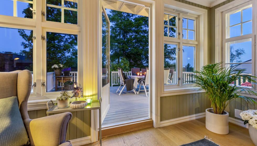 NESTEN UTE: I enden av stua ligger en glassveranda hvor man kan gå rett ut til en stor skjermet terrasse. Foto: Andreas Spinnangr Wiig / Inviso/ DNB Eiendom