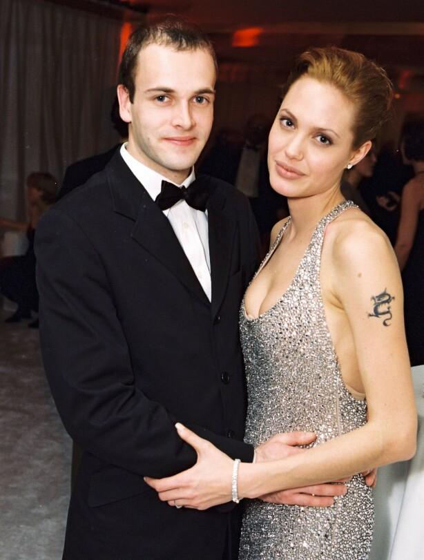 SPESIELT ANTREKK: På bryllupsdagen valgte Angelina Jolie å ha på seg en hvit skjorte med blodskrift på ryggen og svarte gummistøvler. Her er hun avbildet med sin daværende utkårede Jonny Lee Miller i 1999. Foto: NTB Scanpix