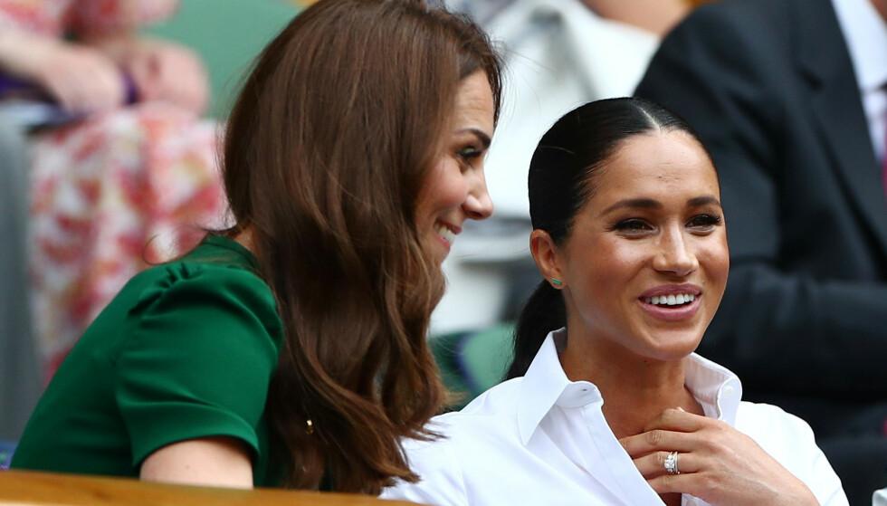 GOD STEMNING: Hertuginne Kate og hertuginne Meghan var i strålende humør der de satt ved siden av hverandre på tribunen. Foto: NTB Scanpix