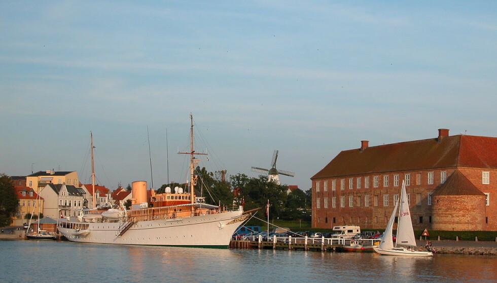<strong>KONGESKIP:</strong> Her ligger «Dannebrog» i havn i Søndeborg. Til høyre ser man sjøsiden av Sønderborg Slott. Foto: Wikimedia Commons.