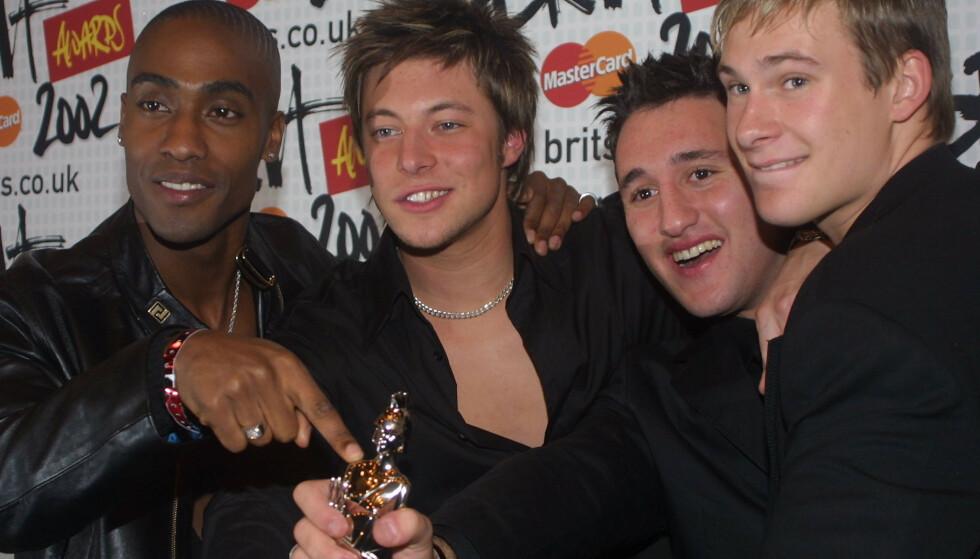 STOLT: Duncan James, som poserer her i midten med dyp kløft, sier han nå er stolt av å være homofil. Her poserer han med resten av gruppa i 2002, da de vant Brit Award for i kategorien «British Brakethrough Act». Foto: NTB scanpix