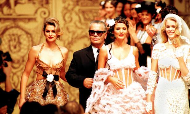 <strong>SUPERMODELL:</strong> Cindy Crawford sammen med designer Karl Lagerfeld, og modellkollegene Helena Christensen og Claudia Schiffer i Paris i januar 1993, da de gikk på catwalken for Chanel. Foto: Lionel Cironneau/ AP/ NTB scanpix