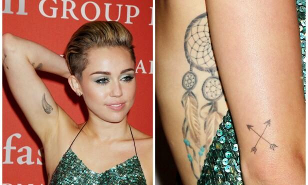 <strong>TATOVERT:</strong> Miley Cyrus har over 20 ulike tatoveringer rundt om på kroppen. Her viser hun frem noen av dem på rød løper i 2013. Foto: NTB scanpix