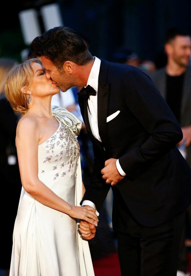 <strong>KLINTE TIL:</strong> Sangstjernen Kylie Minogue stjal et kyss fra sin utkårede, Paul Solomons på den røde løperen. Foto: NTB Scanpix