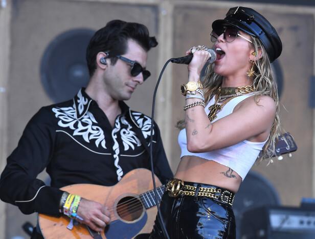 STJERNE: Mark Ronson er musiker, og har blant annet samarbeidet med Miley Cyrus. Her er de to på scenen under årets Glastonbury-festival i England. Foto: NTB Scanpix