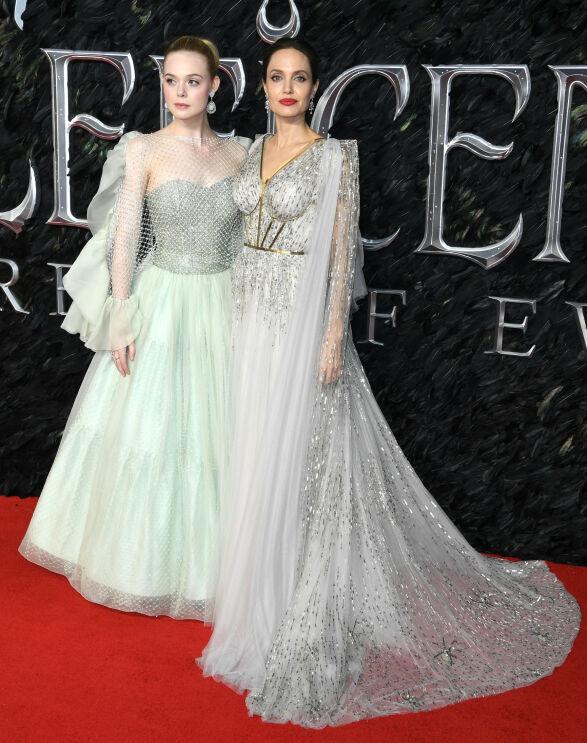 KOLLEGER: Elle Fanning og Angelina Jolie matchet hverandre i lyse, glitrende kjoler på London-premieren. Foto: NTB scanpix