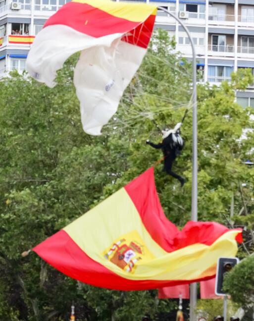 <strong>UHELDIG:</strong> Fallskjermhopper Luis Fernando Pozo ble sittende fast i en lyktestolpe under paraden i Madrid lørdag. Foto: NTB scanpix