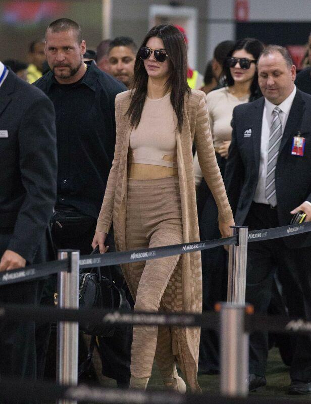 ESKORTE: Også når familien Kardashian/Jenner er på reise, er det med svært omfattende sikkerhetstiltak. Her er Kylie og Kendall avbildet på en flyplass i Melbourne i 2015, omringet av flere sikkerhetsvakter. Foto: NTB Scanpix