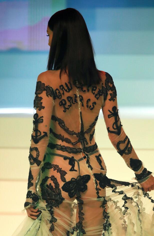 GAULTIER: Bella Hadid hadde på en gjennomsiktig kjole med spennende detaljer. Det sto blant annet skrevet «Gaultier Paris» på ryggen. Foto: NTB Scanpix
