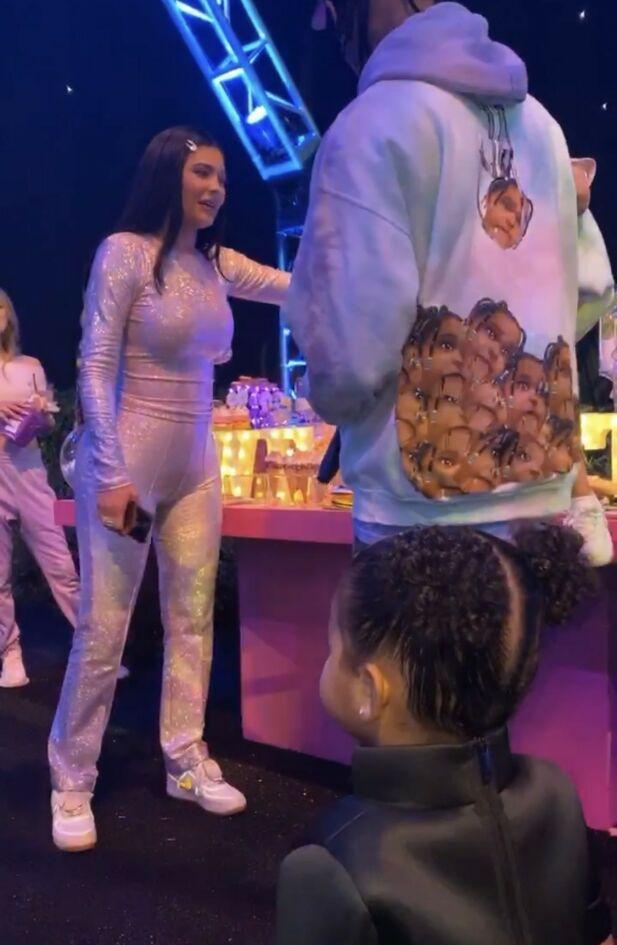 STOLTE FORELDRE: Kylie og Travis samlet seg på festen for å skjære opp kaken. Legg merke til genseren til Travis. I forgrunnen ser man lille True, datteren til Khloé Kardashian. Foto: Instagram