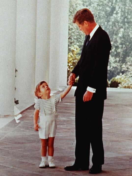 FAR OG SØNN: JFK senior holder sin sønn JFK jr. i hånden utenfor Det Hvite hus. Året er 1963, og presidenten har bare kort tid igjen å leve. Foto: AP / NTB