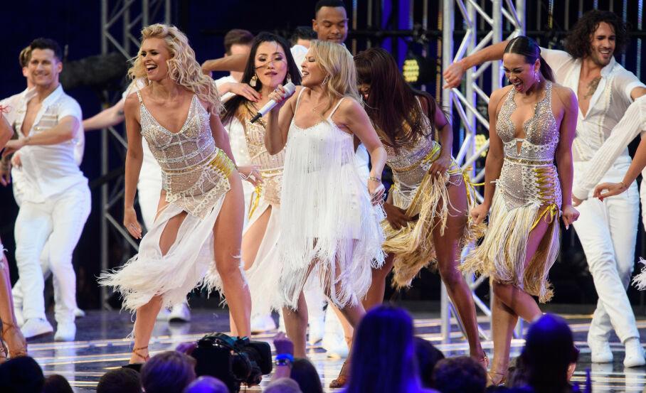 SMITTETRØBBEL: Coronaviruset har stukket uheldige kjepper i hjulene for «Strictly Come Dancing». Her opptrer Kylie Minogue sammen med flere dansere under lanseringen av programmet høsten 2019. Foto: Matt Crossick/ Empics/ NTB scanpix