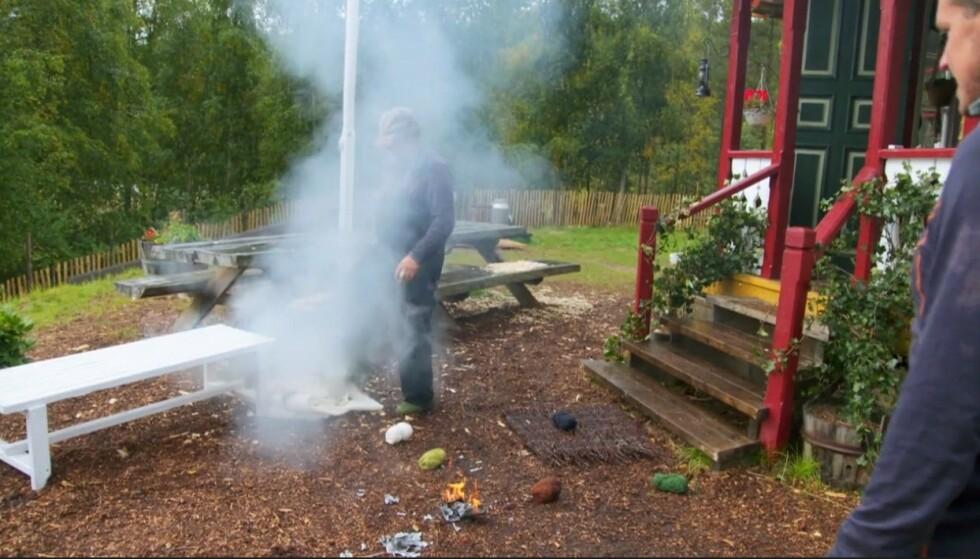 UKESOPPDRAGET RØYK: Bokstavelig talt. Det brennende broderiet ble kastet ut av huset av filmcrewet. Foto: Skjermdump/TV 2