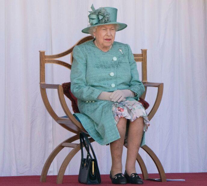 PÅ GULVET: Her har dronninga pent plassert veska på gulvet. Forklaringen skal være at det ikke finnes et bord i nærheten, og at det derfor ikke kan tolkes som et av signalene. Foto: Paul Edwards / POOL / AFP / NTB