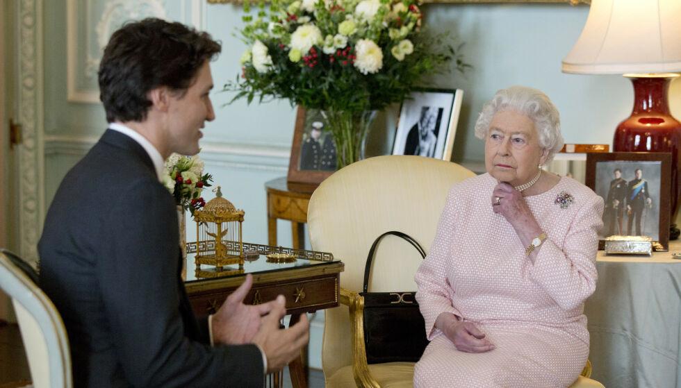 ALLTID MED: Dronning Elizabeth er aldri langt unna sin egen veske. Her deler hun stol med den under et møte med Canadas statsminister, Justin Trudeau. Foto: NTB