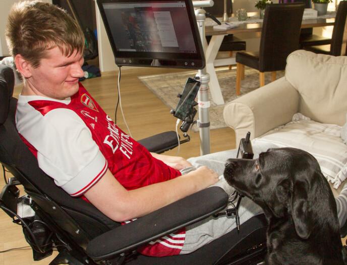 ØYESTYRT: Remi har ikke lenger bevegelse i hendene. Men avansert teknologi gjør det mulig for ham å styre både telefon, datamaskin og fjernkontroll ved hjelp av øynene. Hunden Ailo skjønner ikke helt hvorfor de to ikke lenger kan leke sammen. Foto: Svend Aage Madsen/ Se og Hør.