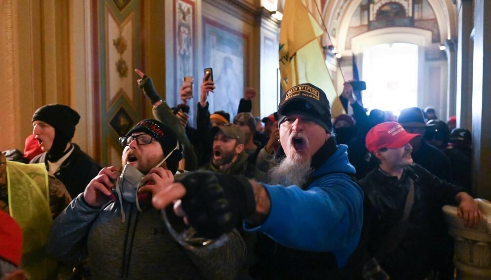 VEKKER REAKSJONER: Dette bildet viser rockestjerne Jon Schaffer (i blått) inne i Kongressens sete under opprøret 6. januar 2021. Foto: Roberto Schmidt / AFP / NTB
