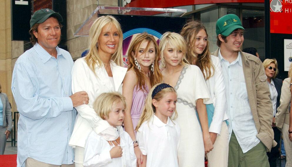 STORFAMILIE: Olsen-familiens seks barn er en god blanding av kjente og ukjente fjes. Her er Mary-Kate, Ashley og Elizabeth Olsen sammen med faren, stemoren, og sine tre mer ukjente søsken i 2004. Foto: REX/ NTB