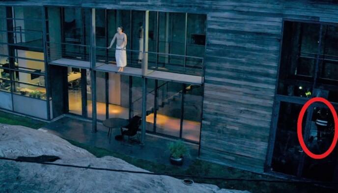 «CHILLER»: Mens Simon J. Berger står på balkongen og reflekterer over livet, står et medlem av filmcrewet i underetasjen og slapper av i refleksvest. Foto: NRK.
