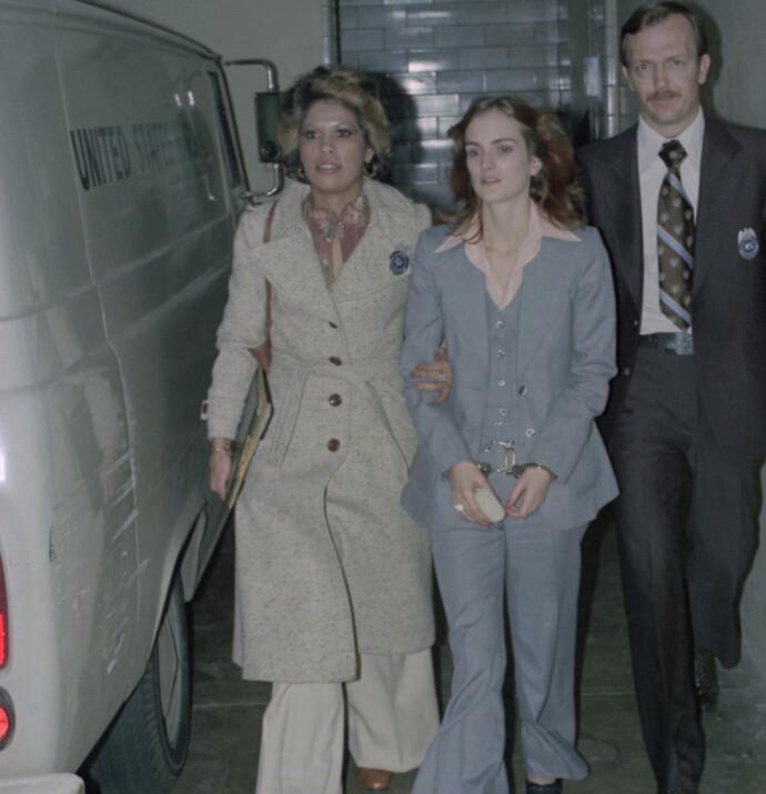 I JERN: Patty Hearst føres ut av San Francisco Federal Building under rettssaken mot henne i 1976. Foto: NTB