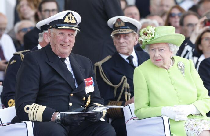 KONDOLERER: Kong Harald avbildet sammen med dronning Elizabeth i 2014. Prins Philip sitter på raden bak. Foto: Terje Bendiksby / NTB