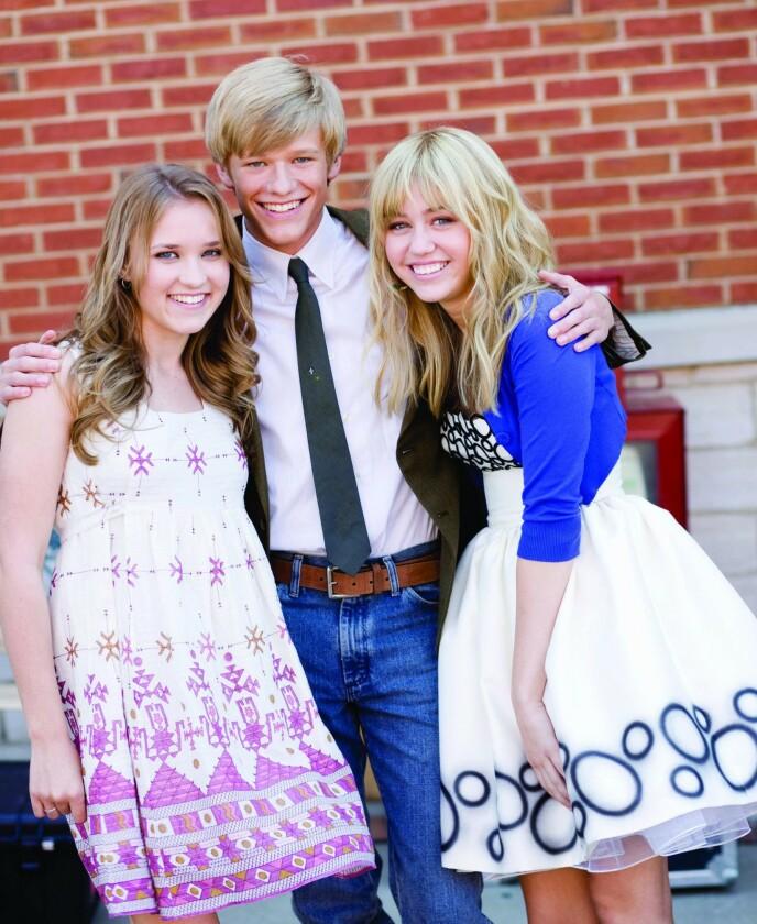 FILM: I filmen «Hanna Montana: The Movie» fra 2009 fikk fansen igjen møte skuespillerne fra serien. Her er Emily Osment, Lucas Till og Miley Cyrus avbildet sammen på filmsettet. Foto: Snap Stills / REX / NTB