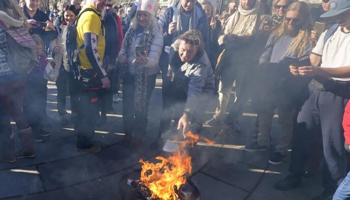 FÅR HARD MEDFART: Svein Østvik brant munnbindet sitt under coronaskeptikernes markering utenfor Stortinget. Foto: Heiko Junge / NTB