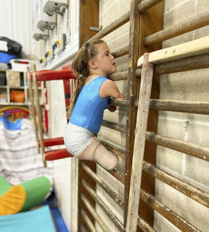 TØFF: Harmonie husker ikke hvordan det var å ha armer og ben – og har lært seg å bruke det hun har. Her klatrer hun i en ribbevegg. Foto: Matt Barbour