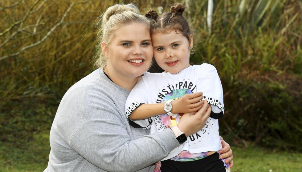 LYKKELIGE: Harmonie Rose sammen med mamma Freya. Med en smart protese kan hun endelig holde mammas hånd. Nå håper hun på en ny protese på sin venstre arm også. Foto: Matt Barbour