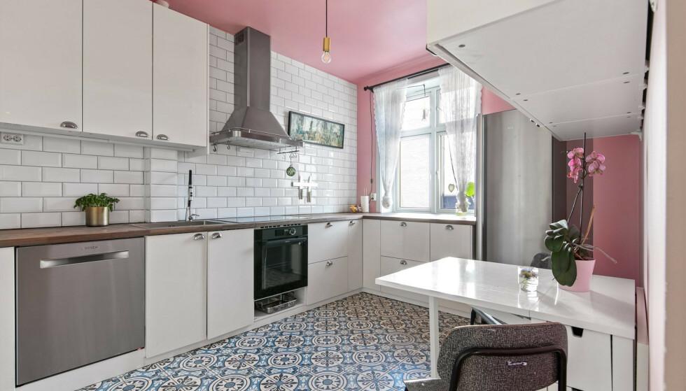 SPREKT: Kjøkkenet er rosa og hvitt, med blålige fliser på gulvet. Foto: Mats Bakken / Inviso AS