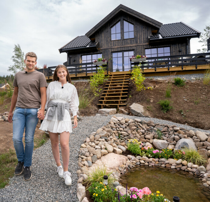 SKAL SELGES: Anna Rosenlund Skretteberg (23) og kjæresten Jone Engemoen Hansen (27) foran hytta de bygget og pusset opp. Foto: Espen Solli / TV 2
