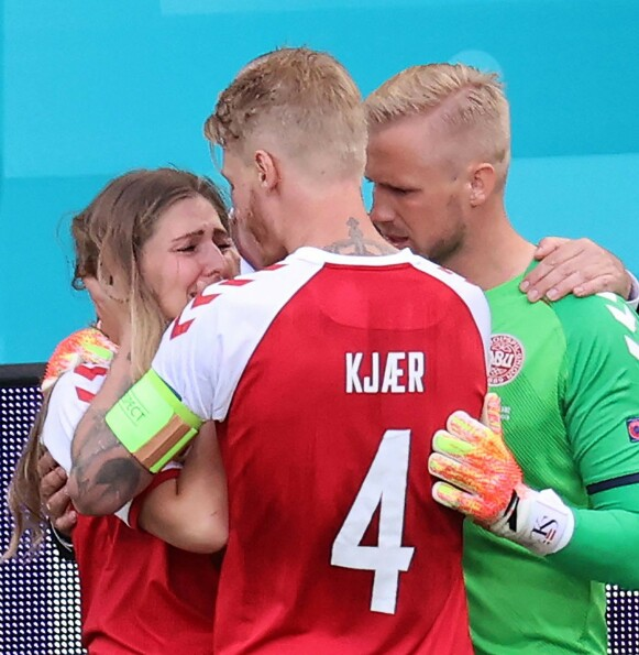 SJOKK: Eriksens kone Sabrina Kvist Jensen ble trøstet av lagkaptein Simon Kjær og keeper Kasper Schmeichel. Foto: WOLFGANG RATTAY / AFP)