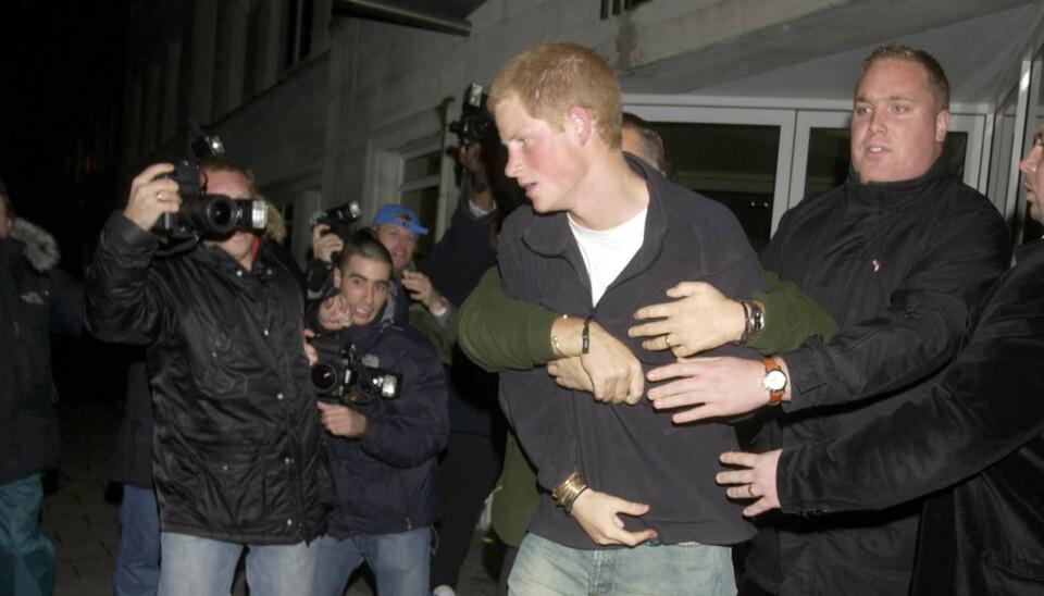 HOLDT IGJEN: Prince Harry havnet i et sammenstøt med en paparazzifotograf i 2004. Det er kun én av mange hendelser fra prinsens liv, som har skapt overskrifter i presse. Foto: David Abiaw/REX/NTB